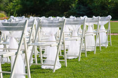 White decorated chairs on a green lawn. Chairs set in rows for the wedding ceremony. They are decorated for the festive event. Chairs are on the green lawn Royalty Free Stock Photos