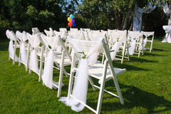 White decorated chairs on a green lawn. Chairs set in rows for the wedding ceremony. They are decorated for the festive event. Chairs are on the green lawn Stock Images