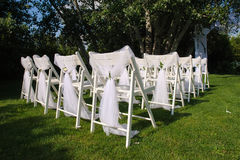 White decorated chairs on a green lawn. Chairs set in rows for the wedding ceremony. They are decorated for the festive event. Chairs are on the green lawn Royalty Free Stock Images