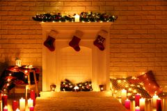 Decorated fireplace with stocking socks. White decorated fireplace with stocking socks on brick wall background stock photography