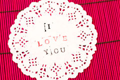 White decorated piece of paper on red wooden surface with the writing I love you Stock Photos