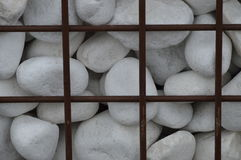 White decoration rocks behind an iron  fence Royalty Free Stock Photo