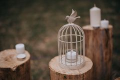 White decorative cage with candle hanging and burning on retro wooden desk with fallen dry leaves stock image