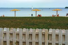 Beach umbrellas made of straw on the background of water and yacht Stock Images