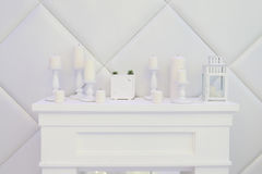 White decorative fireplace, candles, clock Stock Photography