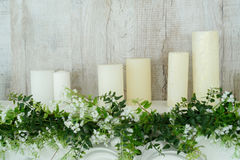 White decorative fireplace with candles on it near wooden wall. Floral decoration of white flowers. And greenery over white fireplace, closeup Stock Photos
