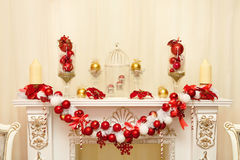 White Decorative fireplace decorated with candles and garlands o Stock Image