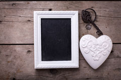 White  decorative  heart, empty blackboard and vintage key on ag Royalty Free Stock Images