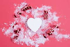 White decorative heart, fake snow and red festive swirls on pastel pink background. Festive concept stock photos