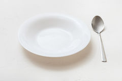 White deep plate and spoon on plaster Stock Photos