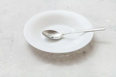 White deep plate with steel spoon on gray concrete Stock Photography