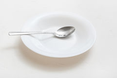 White deep plate with steel spoon on plaster Stock Images