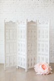 White delicate decorative wood panel with big paper flowers on white brick wall. Boudoir wedding room. Retro folding screen. Vintage ornate carved folding Stock Photos