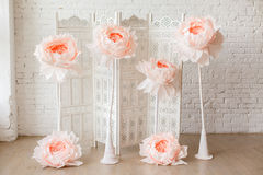 White delicate decorative wood panel with big paper flowers on white brick wall. Boudoir wedding room. Retro folding screen. Vintage ornate carved folding Stock Photo