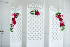 White delicate decorative wood panel in classical interior. Boudoir wedding room. Retro folding screen with flowers Stock Photography