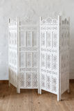 White delicate decorative wood panel on white brick wall. Boudoir wedding room. Retro folding screen. Vintage ornate carved folding screen Stock Photo