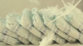 White delicate feathers fall on baby diapers, the concept of comfort and lightness, slow motion. Affectionateness stock footage