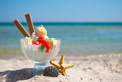 Ice cream candy cookies cream vase starfish shell sand blue sea and blue sky. White delicious dessert ice cream multi-colored candy dragee long biscuits lie in Stock Photography