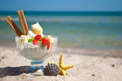 Ice cream candy cookies cream vase starfish shell sand blue sea and blue sky. White delicious dessert ice cream multi-colored candy dragee long biscuits lie in Royalty Free Stock Photo