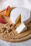 White delicious homemade camambert cheese on a wooden plate served with almonds, cashew, pine nuts and peach. Royalty Free Stock Photo