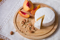 White delicious homemade camambert cheese on a wooden plate served with almonds, cashew, pine nuts and peach. Royalty Free Stock Photography