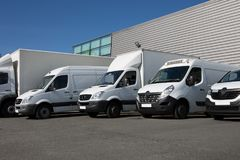 White Delivery van transportation truck park. White Delivery Trucks Backed Up to A Warehouse Building Stock Photos