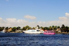 White deluxe yacht and pink taxi, South Florida Royalty Free Stock Image