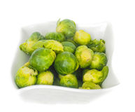 White designer bowl with fresh green brussels sprout. Isolated on white Royalty Free Stock Image