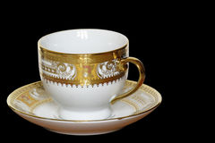 White designer cup and saucer isolated on black Royalty Free Stock Photos