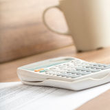 White desk calculator on a document next to a mug Royalty Free Stock Image