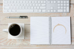 White Desk With Coffee and Keyboard. High angle shot of a white rustic desk with a modern keyboard, coffee cup and notebook with a coffee stain. Horizontal Stock Images