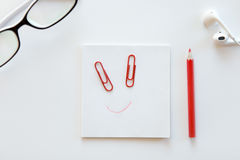 White desk with paper block, a drawn smile on it stock photo