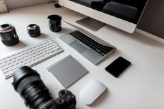 White desktop of a designer with a laptop with a mouse with a modern professional camera with a keyboard with a laptop. White desktop of al designer with a royalty free stock images