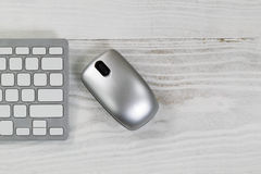 White desktop with silver wireless mouse and partial keyboard Royalty Free Stock Photography