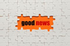 White details of puzzle on orange background and word Good news Stock Photos