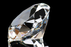 White Diamond on Black Background. Horizontal image of a white diamond and its reflection with the table facing to the left upper corner on a black background Royalty Free Stock Images