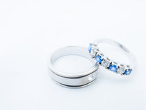 White diamond and blue gemstones on white gold wedding rings wit Royalty Free Stock Photos