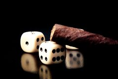 White dice and cigar on old wood table Royalty Free Stock Image