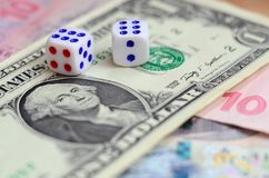 White dice are on a dollar bill of US dollars. The concept of gambling with rates in monetary unit. S stock photos
