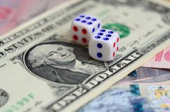 White dice are on a dollar bill of US dollars. The concept of gambling with rates in monetary unit. S royalty free stock photo