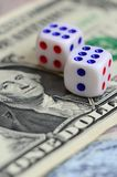 White dice are on a dollar bill of US dollars. The concept of gambling with rates in monetary unit. S royalty free stock photography
