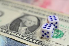 White dice are on a dollar bill of US dollars. The concept of gambling with rates in monetary unit. S stock photo