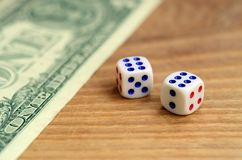 White dice are next to a dollar bill of US dollars on a wooden background. The concept of gambling with rates in monetary unit. S royalty free stock photo