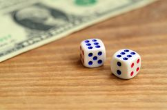 White dice are next to a dollar bill of US dollars on a wooden background. The concept of gambling with rates in monetary unit. S stock photo