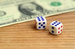 White dice are next to a dollar bill of US dollars on a wooden background. The concept of gambling with rates in monetary unit. S stock photos