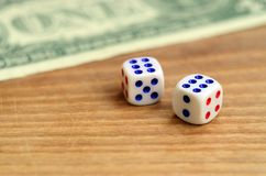 White dice are next to a dollar bill of US dollars on a wooden background. The concept of gambling with rates in monetary unit. S stock photography