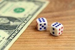 White dice are next to a dollar bill of US dollars on a wooden background. The concept of gambling with rates in monetary unit. S royalty free stock photos
