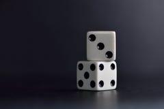 White dice pair on black background. Closeup stock image