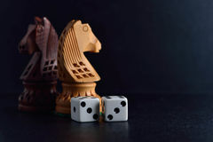 White dice pair and chess knights on black background. Closeup stock photo
