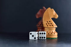 White dice pair and chess knights on black background. White dice pair on black background closeup royalty free stock photo